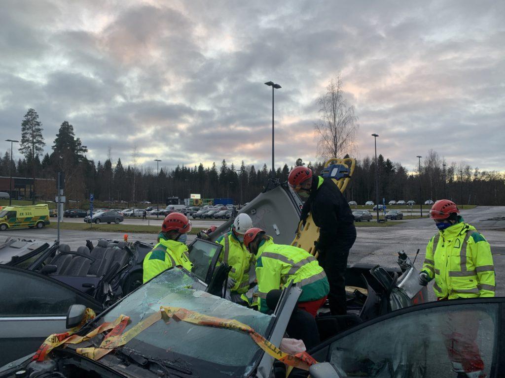 Ensihoitajat ja palomiehet harjoittelevat potilaan evakuoimista liikenneonnettomuuteen joutuneesta autosta.
